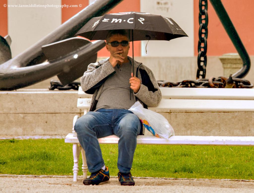Man with umbrella with E = MC2 written on it in Kongresni Square, Ljubljana, Slovenia.