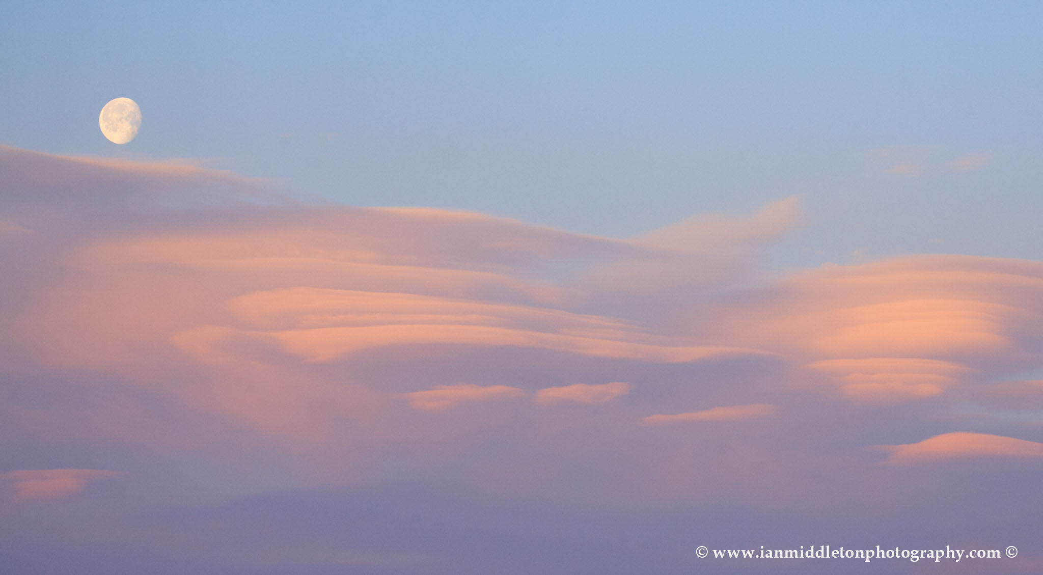 Lenticular cloud formation (Altocumulus lenticularis) at sunrise with the waning moon setting above then over residential area of Ljubljana taken from a sixth floor apartment , Slovenia